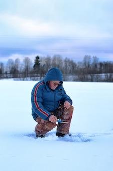 Winter season old man fishing on a lake