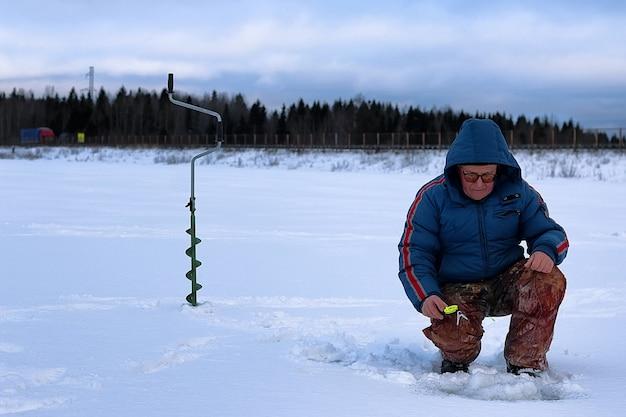 호수에서 낚시하는 겨울 시즌 노인 프리미엄 사진
