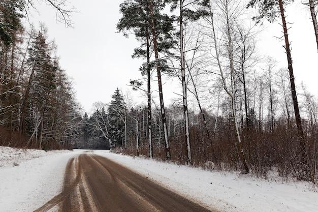 冬の季節。雪道に覆われた小さな田舎道に沿って森の木々が生えています。近づきました。汚れやビジョンカーストリップの道路上