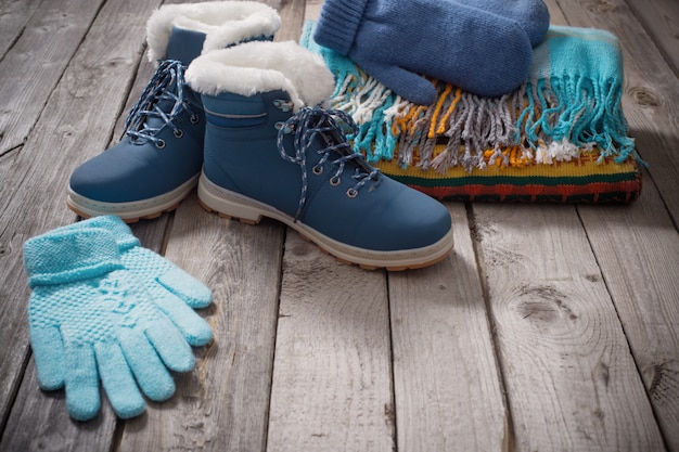 Winter shoes, gloves, scarves  on old wooden background