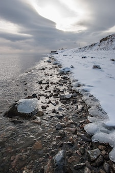 Winter shore of lake baikal with ice at water edge and ice on stones in water