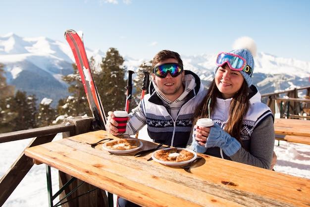 Зима, лыжники - лыжники наслаждаются обедом в зимних горах.