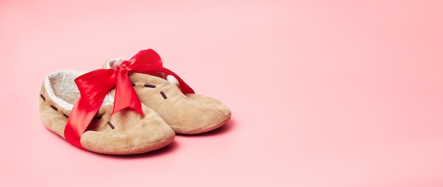 Winter slippers with fur in a red ribbon, on a blue background, banner, copy space, mock up