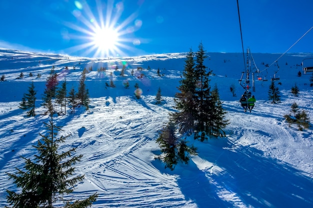 Winter slovakia. ski resort jasna. bright sun over an unequipped ski slope. view from the chair lift