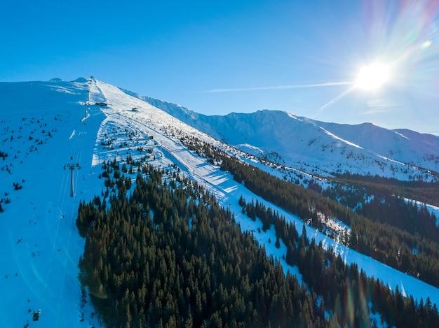 冬のスロバキア。晴天のスキーリゾートジャスナ。樹木が茂った山々のスキー場。青い空に太陽が明るく輝いています。航空写真