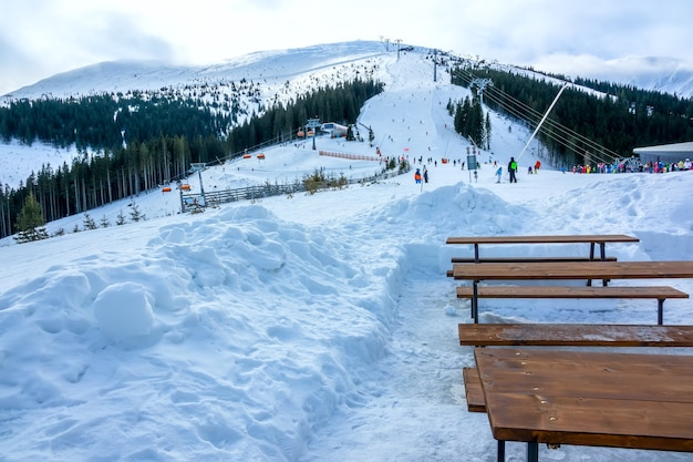 Winter slovakia. ski resort jasna. overcast. empty wooden benches and tables near ski slope
