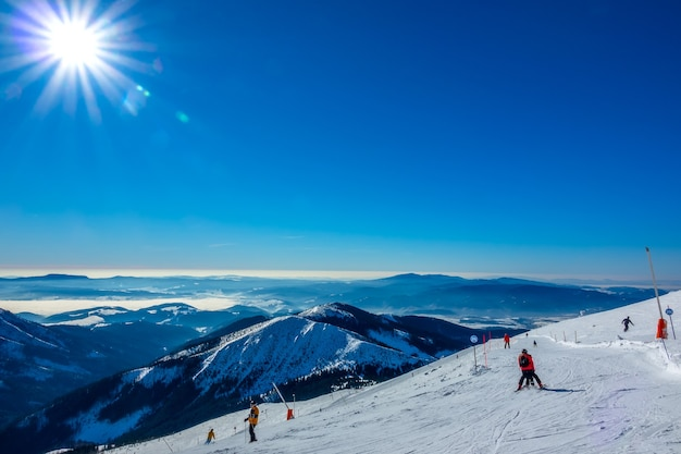 Winter slovakia. ski resort jasna. panoramic view from the top of the snow-capped mountains and ski slope with skiers