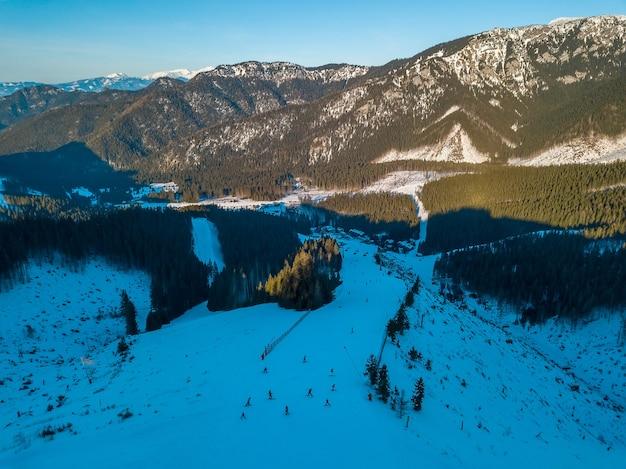 冬のスロバキア。ジャスナスキーリゾートでの晴れた日。青空。山頂とスキー場。航空写真