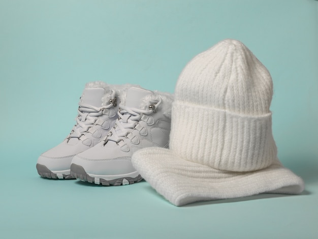 Winter sneakers with fur, hat and scarf on a blue surface