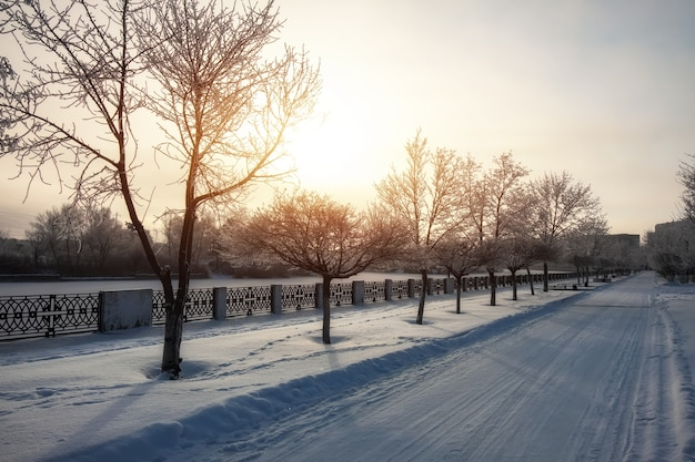 Winter snow-covered city landscape. beautiful sky with a bright sun. road in the snow