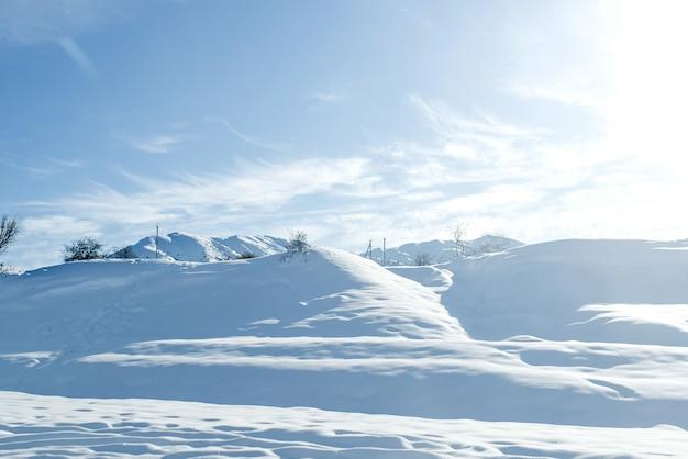 晴天のウズベキスタンの天山山脈の丘は冬の雪で覆われていました
