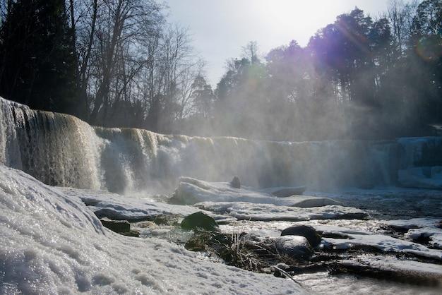Зимние снежные пейзажи, замерзший водопад и сосульки, ледяной водопад холодной реки в дневное время
