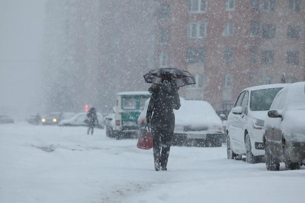 도시의 겨울 강설량과 눈보라: 사람들은 포장도로를 걷는 우산으로 폭풍우로부터 보호합니다.