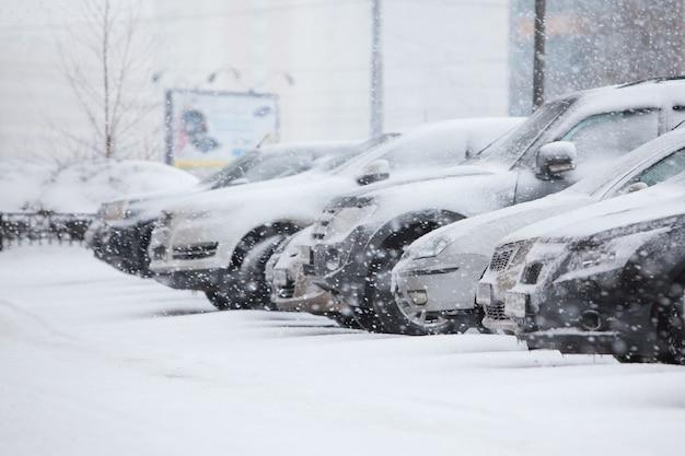 겨울 눈보라: 도시에서 눈보라가 몰아치는 동안 사람들이 운전을 피하면서 눈으로 덮인 자동차