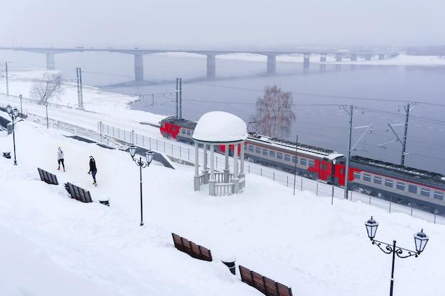 Зимний снежный пейзаж с электропоездом, движущимся по берегу реки