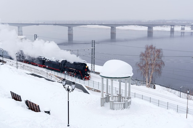 Winter snowy landscape with steam locomotive moving along the river bank