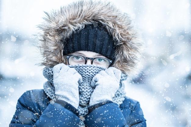 暖かい服を着た少女の冬の雪の肖像画
