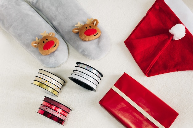 サンタの帽子と白い背景の上の贈り物と冬の靴下。自宅でのクリスマス休暇。
