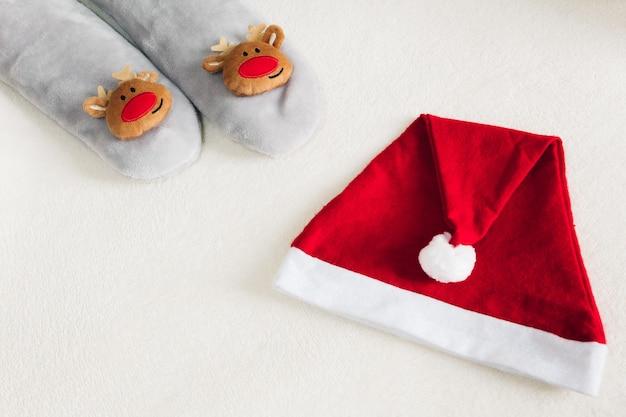 白い背景の上のサンタの帽子と冬の靴下。自宅でのクリスマス休暇。