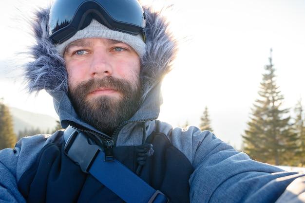 Концепция зимы, спорта и людей - сноубордист-фрирайдер стоит на крутом склоне горной вершины и делает селфи-портрет с камерой или смартфоном на фоне заснеженных гор на горнолыжном курорте