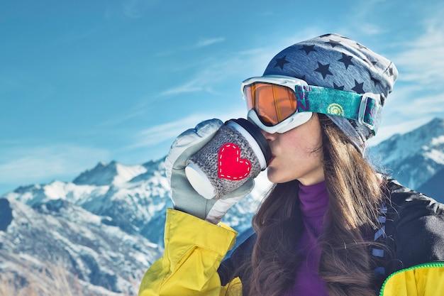하트 그림이 있는 종이컵으로 마시는 겨울 스포츠 소녀