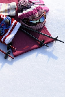 Winter sports background with ski poles, goggles, hats and gloves