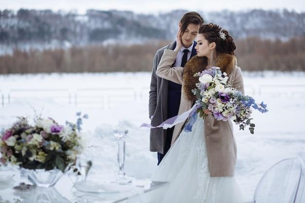 Зимняя постановка свадебной фотографии. жених и невеста с красивым букетом рядом со стеклянным столом и стульями
