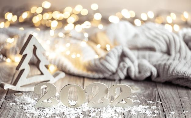 Зимний натюрморт с декоративным номером наступающего года на деревянной поверхности с декоративными элементами на размытом фоне.