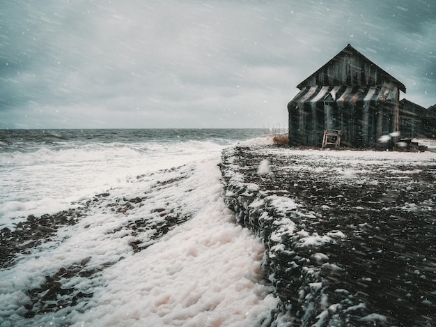 Winter storm day at sea. dramatic seascape with a raging white sea and a fishing hut on the shore. kandalaksha bay. russia.