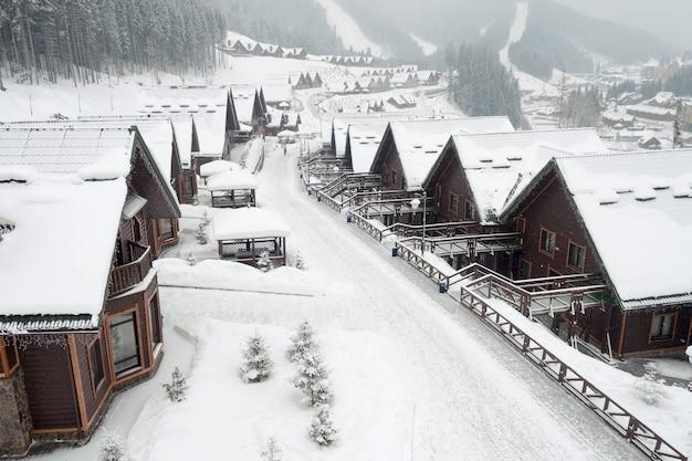 Winter street in alpine village under snowfall