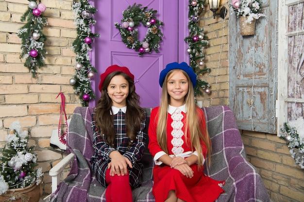 겨울 스타일은 편안함과 따뜻함에 관한 것입니다. 귀여운 아이들은 크리스마스 분위기를 느낍니다. 여자 겨울 스타일입니다. 겨울 시즌을 위한 패션 스타일을 가진 어린 소녀들. 크리스마스 장식에 작은 아이 들.