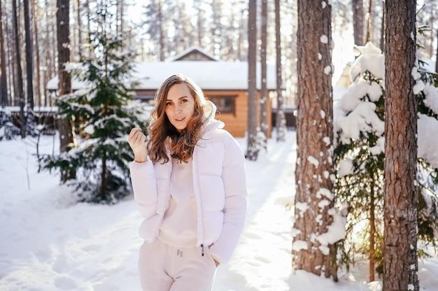국가 목조 주택 뒷마당에서 흰색 따뜻한 착실히 보내다 다운 재킷에 아름 다운 젊은 여자의 눈에 겨울 맑은 차가운 초상화