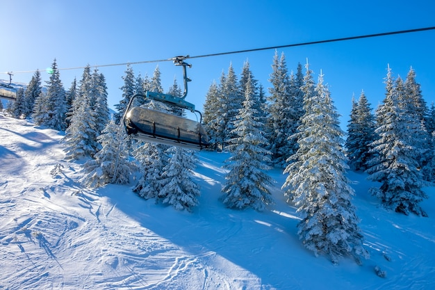 Зимний солнечный день на склоне горы. снежные ели и пустые кабинки кресельного подъемника