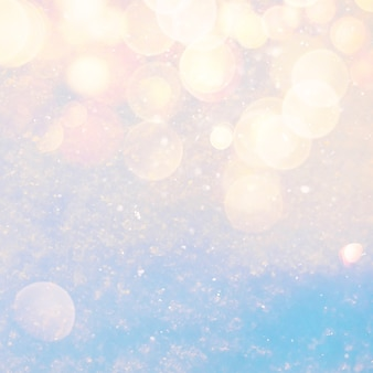 Winter sunny snow texture background with warm lens flare bokeh lights
