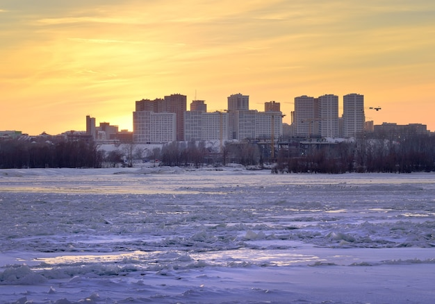 Winter sunset on the banks of the ob river new residential area gorsky on the river bank