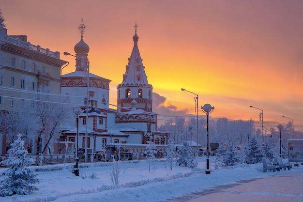 Зимний закат пейзаж морозных деревьев, белый снег в городском парке.