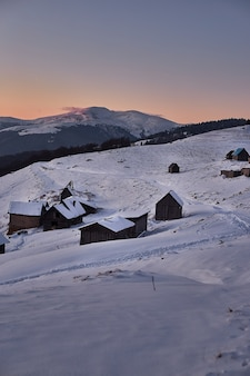 눈 덮인 산에 목조 주택으로 겨울 일몰 풍경