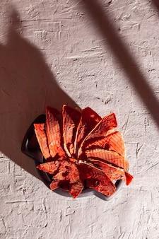 Зимние принадлежности: кусочки сушеного арбуза в деревянной тарелке на белом фоне с глубокой тенью.