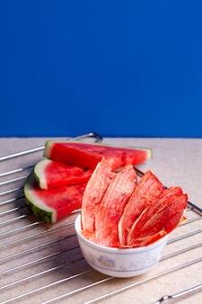 Зимние принадлежности: кусочки сушеного арбуза со свежими кусочками на светлом фоне с сеткой.
