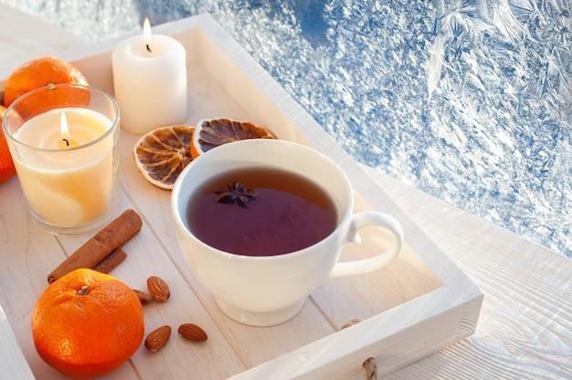 서리가 내린 창에서 겨울 차. 흰색 나무 쟁반에 흰색 컵에 귤, 계 피, 견과류와 차. 고품질 사진