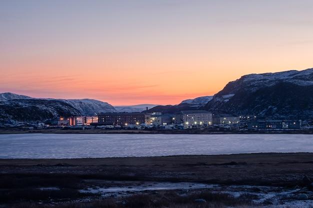 Зимняя териберка. вечерний полярный пейзаж с поселком лодейное, расположенным между полярными холмами.