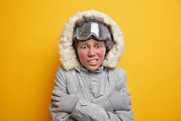 겨울철과 추위 개념. 얼어 붙은 여성이 떨리고 눈보라가 치는 동안 몸을 따뜻하게하기 위해 손을 몸 위로 뻗고 재킷을 입고 산에서 스키를 타며 눈으로 덮인 스키 고글