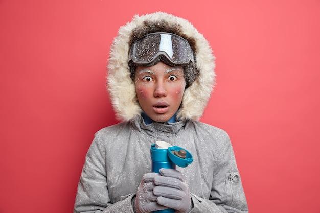겨울 시간 개념. 붉은 얼굴을 가진 놀란 젊은 민족 여성은 따뜻한 재킷을 입고 후드는 좋아하는 취미에 자유 시간을 보내고 스키 또는 스노우 보드를 타는 것입니다.
