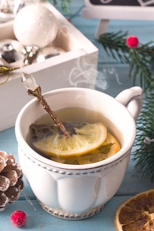 Winter time. cup of hot tea with lemon, christmas toys and woolen scarf. close up
