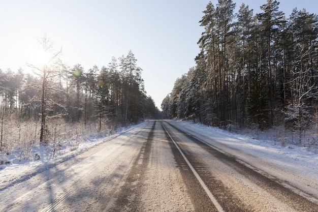 Winter time on a narrow road in the forest, the road is covered with snow after snowfall, frosty weather on a slippery and dangerous road for transport