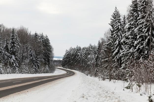 Зимнее время года в снежную погоду, зимняя асфальтированная дорога для автотранспорта