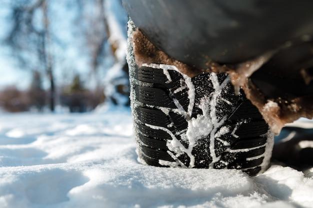 겨울 타이어. 눈 도로에 차. 눈 덮인 고속도로 세부 사항에 타이어. 프리미엄 사진