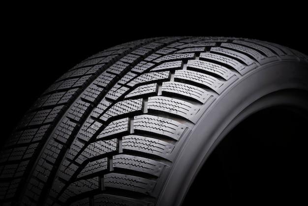 Зимняя шина, безопасность вождения на заснеженных и обледенелых дорогах. асимметричный рисунок протектора. крупным планом на черном фоне.