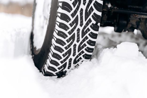 極寒の冬用タイヤ。雪に覆われた道路上の冬の車のタイヤのクローズアップ。輸送の概念