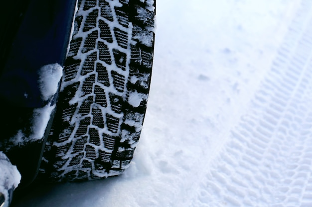 Зимняя резина на колесах авто зимой. снегопад за городом